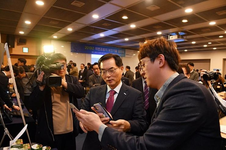 Korea Minting, Security Printing & ID Card Operating Corp. (KOMSCO) CEO Cho Yong-man demonstrates the state-run organization's latest anti-counterfeit technology during a press conference in Seoul, Thursday. Courtesy of KOMSCO