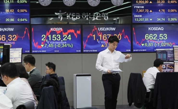 An exchange dealer reads a document ahead of a show displaying the benchmark KOSPI at an office in Seoul, last week. Yonhap