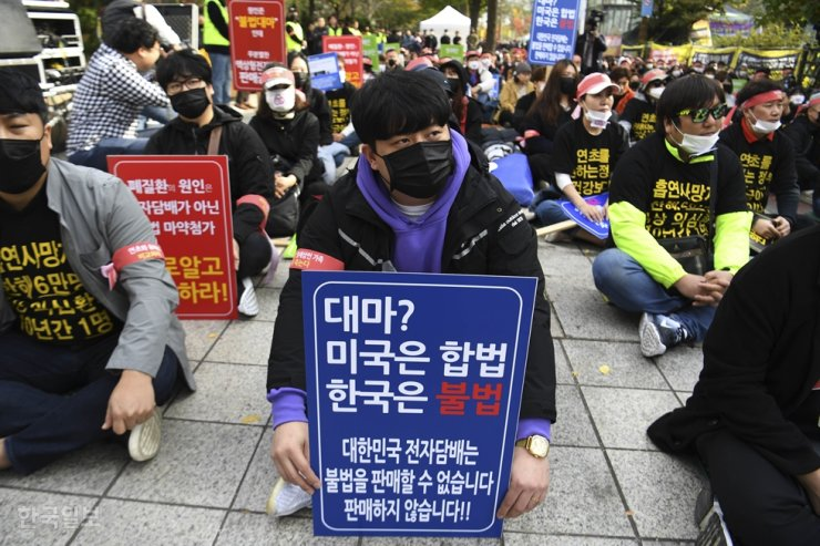 Members of the Korea E-Cig Industry Association protest the government's recent strong warning against the use of liquid e-cigarettes over health concerns, during a rally in front of the National Assembly in Seoul, Wednesday. They demanded the government present scientific evidence to show e-cigarettes are more harmful than combustible ones. / Yonhap