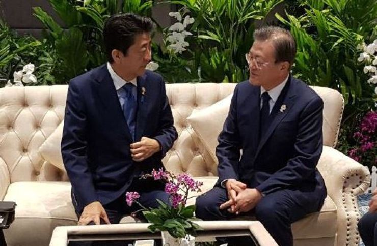 President Moon Jae-in, right, and Japanese Prime Minister Shinzo Abe have a 'pull-aside' meeting ahead of the ASEAN+3 summit in Bangkok, Monday. Yonhap