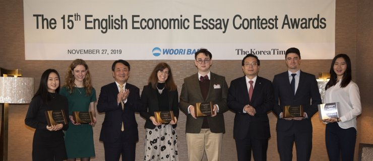 Korea Times President-Publisher Lee Byeong-eon, third from left, and Woori Financial Group Chairman Son Tae-seung, third from right, applaud after giving awards to the winners of the 15th English Economic Essay Contest, at the Lotte Hotel Seoul, Wednesday. From left are Chang Bo-mi, Olivia Truesdale, Lee, Kirsty Goodman, Kim Young-il, Son, Jonathan Humphrey and Paik Ji-won. Runner-up awardee Wee So-yeon was unable to attend the ceremony. / Korea Times photo by Choi Won-suk