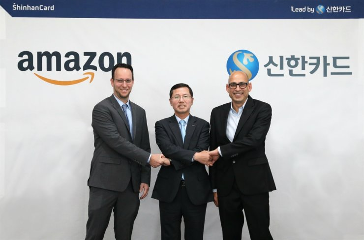 Shinhan Card CEO Lim Young-jin, center, shakes hands with Amazon Global Export head Rotem Hershko, left, and Amazon Global Business Development head Bharat Maheshwari, at Shinhan Card headquarters in Seoul, Nov. 7. Courtesy of Shinhan Card