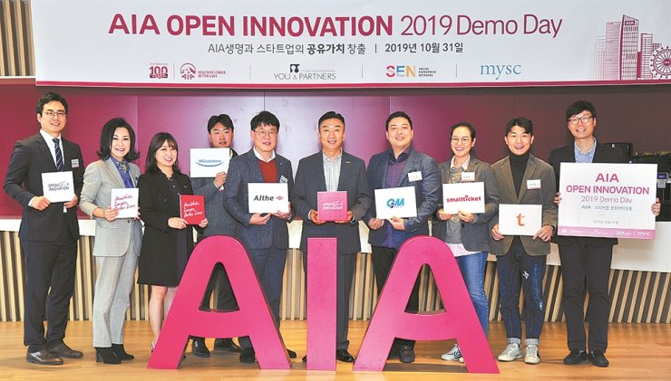 AIA Korea CEO Cha Tae-jin, center, poses with participants of the second round of AIA Open Innovation at the life insurer's headquarters in central Seoul, Oct. 31. The Korean unit of the global insurance group held a demo day for startups in the insurance industry to wrap up the year-long program, which is part of its CSR activities. / Courtesy of AIA Korea