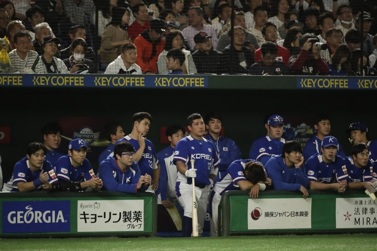 South Korea players watch from the dugout during the ninth inning of the Premier12 baseball tournament final game against Japan at Tokyo Dome in Tokyo Sunday, Nov. 17, 2019. AP