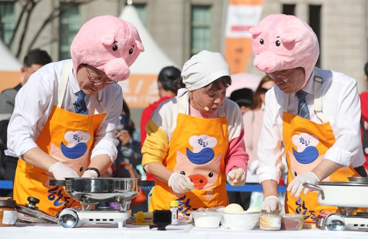 Gyeonggi Provincial Governor Lee Jae-myung, left, and Seoul Mayor Park Won-soon, right, cook pork with help from actress Kim Su-mi at Seoul Plaza, during an event Friday, to encourage people to eat pork. Pork consumption and sales have declined significantly after the outbreak of African swine fever here as people are shunning pork over safety fears. Yonhap
