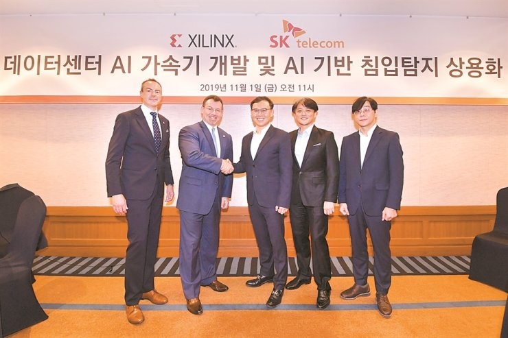 Lee Kang-won, center, vice president and head of cloud at SK Telecom, poses with Sam Rogan, second from left, vice president of APAC regional sales at Xilinx during a press conference at the Grand InterContinental Seoul Parnas hotel, Friday. / Courtesy of Xilinx
