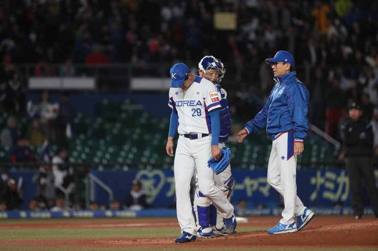 Korean starting pitcher Kim Kwang-hyun, left, leaves the mound after allowing multiple hits during a game against Taiwan at the World Baseball and Softball Confederation Premier 12 in Japan, Tuesday. /Yonhap