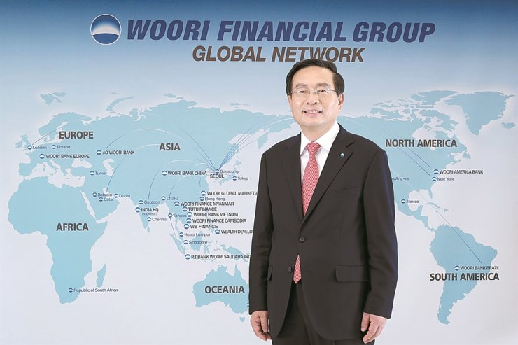 Woori Financial Group Chairman Sohn Tae-seung stands in front of the group's global network map at its headquarters in central Seoul, in this photo provided by the group, Monday. / Courtesy of Woori Financial Group