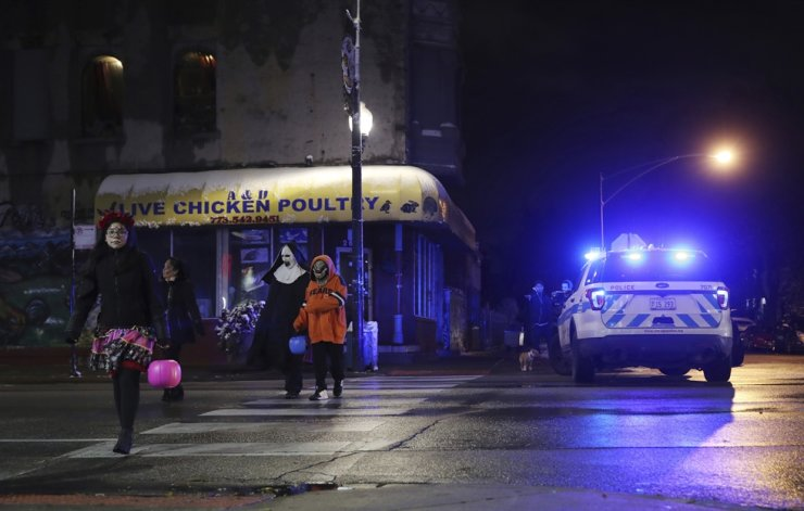 Trick-or-treaters walk past a crime scene in the 3700 block of West 26th Street, where a 7-year-old girl was shot while trick-or-treating Thursday, Oct. 31, 2019, in Chicago. AP