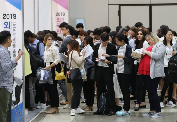 Foreigners look at brochures at a job fair for foreign residents at COEX, Seoul, in this September photo. / Yonhap