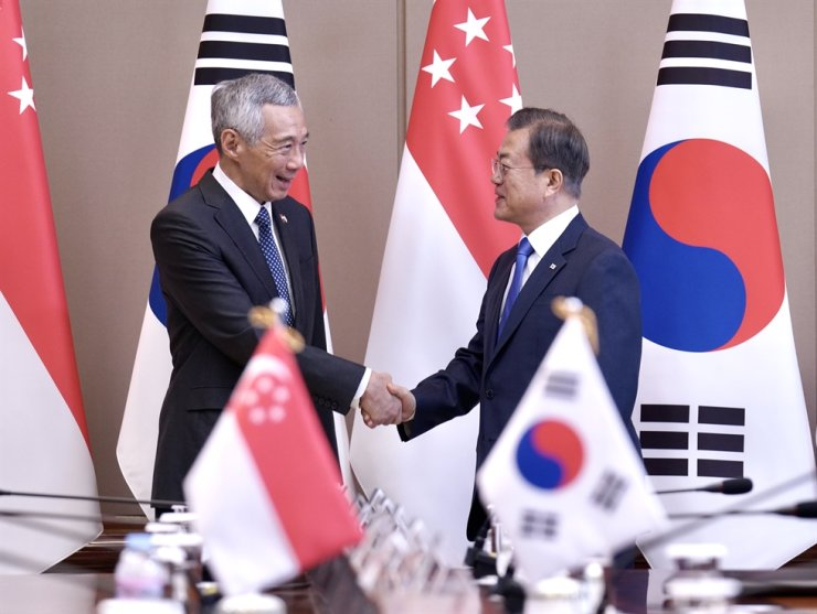 President Moon Jae-in, right, shakes hands with Singapore's Prime Minister Lee Hsien Loong at Cheong Wa Dae, Saturday. Yonhap
