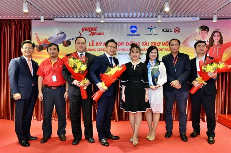 Woori Bank's Ho Chi Minh branch manager Kim Kyu-baek, left, and the bank's head of global investment banking Lee Sang-min, fourth from left, pose with Vietjet CEO Nguyen Thi Phuong Thao, fifth from left, and other guests after the two firms held a ceremony on the lender's financing for the air carrier, at Vietjet's headquarters in Ho Chi Minh City, Nov. 15. The bank provided $140 million in funds for Vietnam's top low-cost carrier, becoming the first local bank to engage in aircraft financing for a private airline company in the Southeast Asian country. / Courtesy of Woori Bank