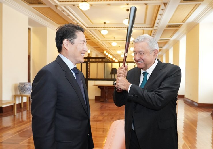 Hyosung Group Chairman Cho Hyun-joon, left, presents a baseball bat to Andres Manuel Lopez Obrador, president of Mexico, as a gift at the National Palace in Mexico City, Wednesday. The company said its ATM manufacturing arm Hyosung TNS will supply 8,000 bank machines worth 203 billion won ($174 million) for Mexico's Rural ATM Project by the end of 2020. / Yonhap