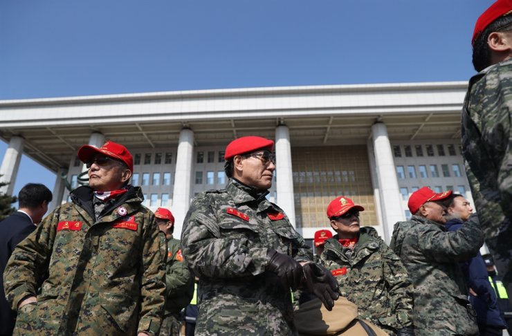 'Taegeukgi Rally' protestors in military uniforms stand in front of the National Assembly Mar. 2, 2017, a week before the Constitutional Court upheld the parliamentary impeachment vote on President Park Geun-hye. / Yonhap