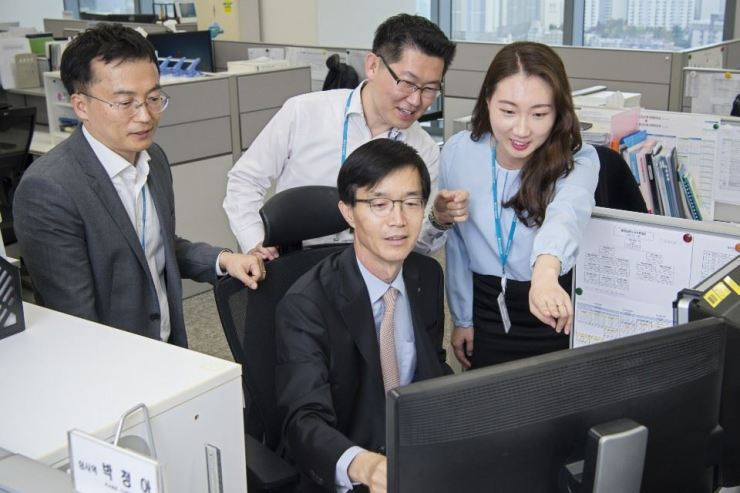Export-Import Bank of Korea (Eximbank) CEO Bang Moon-kyu, center, tries to grant loans to customers using a computerized processing system at the state-run lender's Busan branch, Monday. / Courtesy of Eximbank