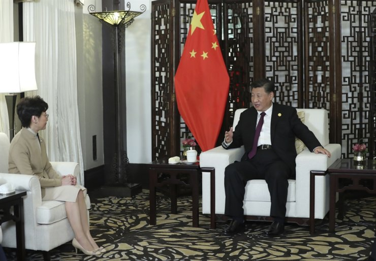 In this Monday, Nov. 4, 2019, photo released by China's Xinhua News Agency, Chinese President Xi Jinping, right, talks with Hong Kong Chief Executive Carrie Lam during a meeting in Shanghai, China. AP