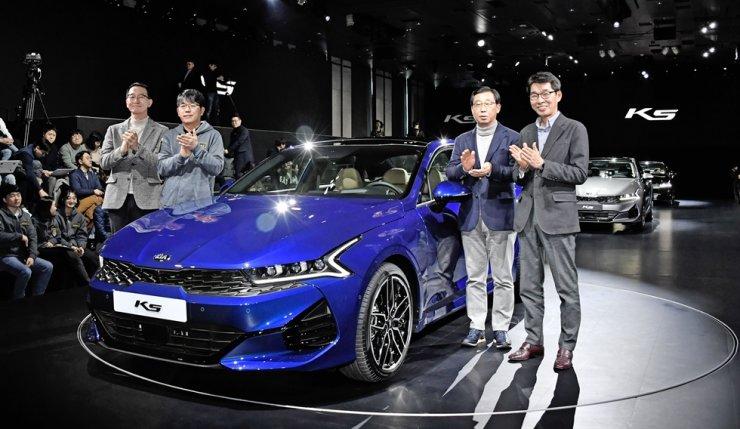 Kia Motors CEO Park Han-woo, third from left, poses with the new K5 midsize sedan during its launch event at the Grand Walkerhill Seoul hotel in Gwangjin-gu, Thursday. Courtesy of Kia Motors