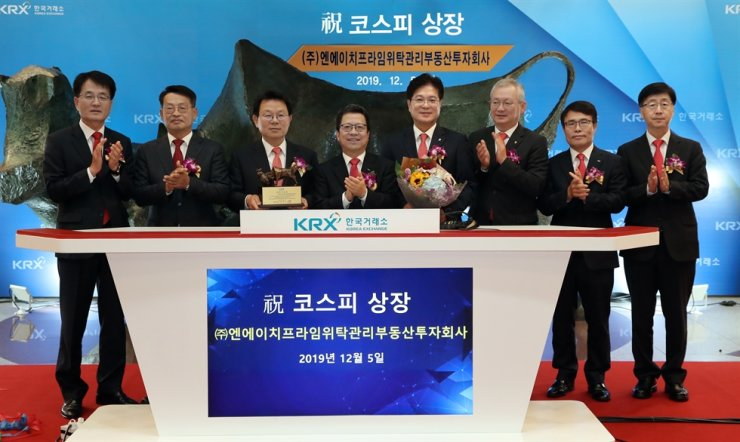 NH NongHyup Financial Group Chairman Kim Kwang-soo, third from left, poses with Korea Exchange President Chung Ji-won, fourth from left, and other guests after NH Prime REIT went public on the KOSPI in Seoul, Thursday. Courtesy of Korea Exchange