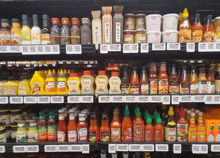 Various foreign condiments, including guacamole, once rare in Korea, are on the shelves at a supermarket in Seoul, Dec. 29. / Korea Times photo by Jon Dunbar