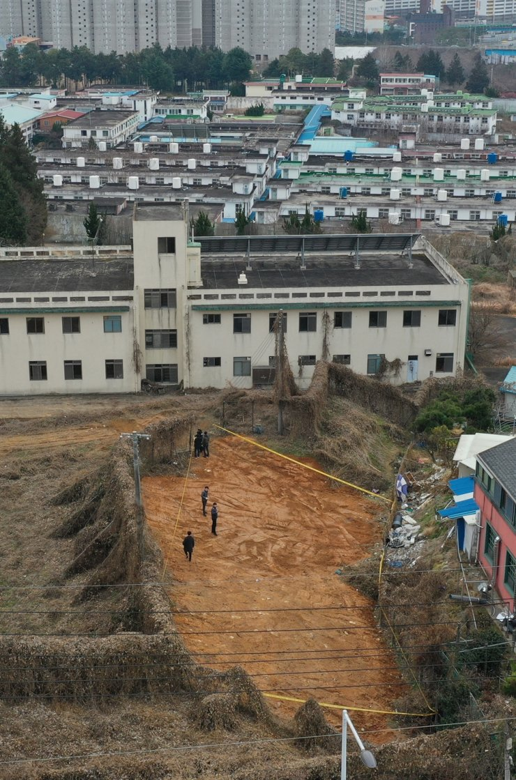 Police officers inspect a graveyard site Friday at a former prison in Gwangju where dozens of unidentified bodies were found. Yonhap