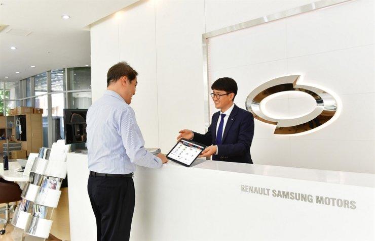 A Renault Samsung Motors staffer speaks to a customer using the firm's mobile-based sales management system, e-BEST. / Courtesy of Renault Samsung Motors