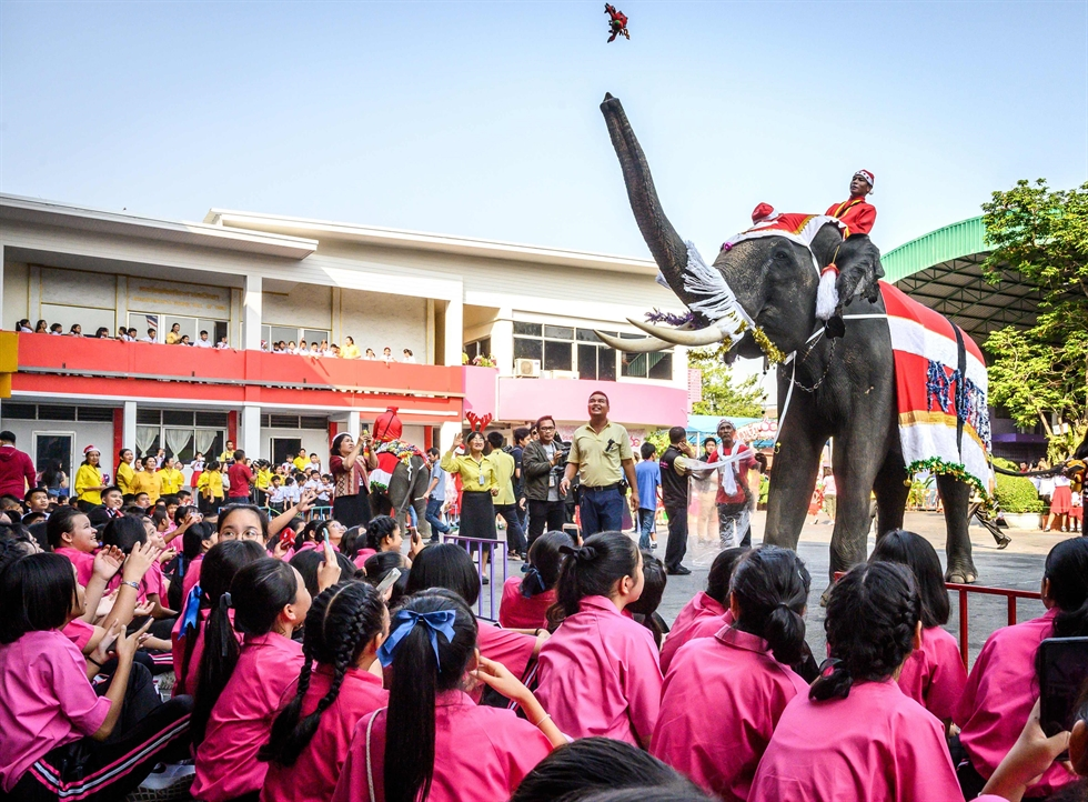 An elephant dressed in a Santa Claus costume presents gifts to schoolchildren during Christmas celebrations in Ayutthaya on Dec. 23, 2019. /AFP