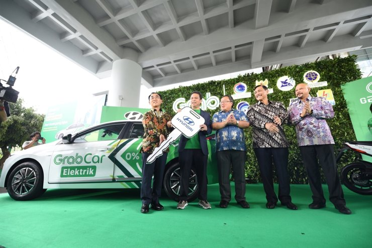 Hyundai Motor Manufacturing Indonesia Director Choi Yoon-seok, left, with Grab Indonesia Managing Director Ridzki Kramadibrata, second from left, and Indonesian government officials in front of Ioniq Electric in Jakarta, Friday. / Courtesy of Hyundai Motor