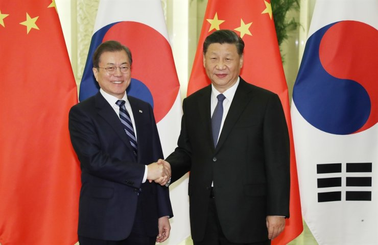 President Moon Jae-in, left, shakes hands with Chinese President Xi Jinping ahead of their summit meeting in Beijing, Monday. Yonhap