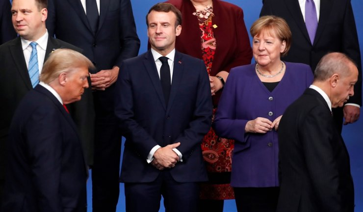 France's President Emmanuel Macron, second from left, and Germany's Chancellor Angela Merkel, look at U.S. President Donald Trump and Turkey's President Recep Tayyip Erdogan during a 'family' photo at the NATO summit at the Grove hotel in Watford, northeast of London, Dec. 4. AFP-Yonhap