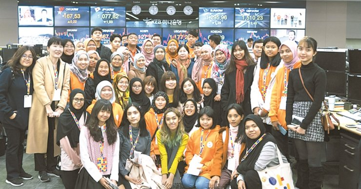 Students from 10 ASEAN countries pose after learning about foreign exchange trading at KEB Hana Bank's headquarters in central Seoul, Nov. 27. Hana Financial Group invited 100 students from the region for its finance education program on the occasion of the Korea-ASEAN Commemorative Summit held in Busan, Nov. 25 and 26. / Courtesy of Hana Financial Group