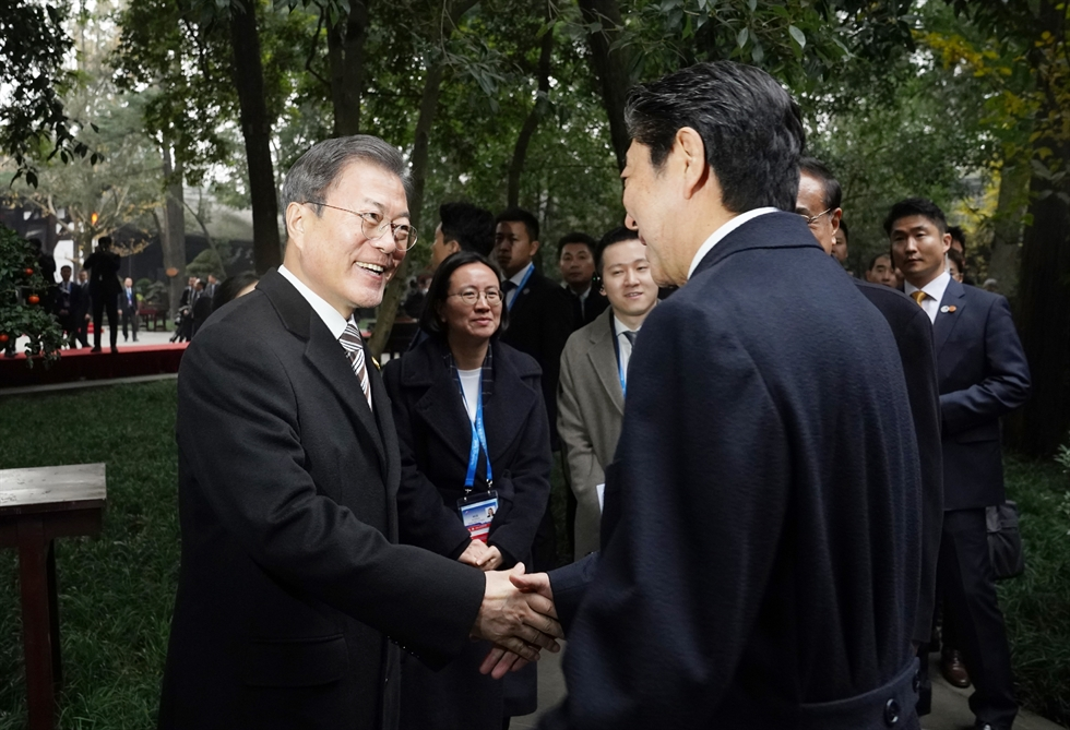 President Moon Jae-in, left, shakes hands with Japanese Prime Minister Shinzo Abe before their summit at Shangri-La Hotel in Chengdu, China, Tuesday. Yonhap