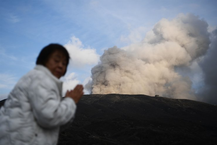 A woman stands near Mount Aso, an active volcano, in the city of Aso, in Kumamoto prefecture on Dec. 14, 2019. Mount Aso's huge caldera dominates the southwestern main island of Kyushu, where the 1,592-metre (5,253-foot) volcano is a popular tourist spot. AFP
