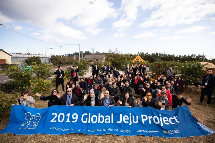 Foreign delegates and staff who have participated in the 2019 Global Jeju Project hosted by the Jeju Special Self-Governing Province and the Jeju Tourism Organization pose for a photo at a tangerine farm in Hahyo village in Seogwipo, Jeju, Dec. 7, the first day of the two-day tour program on Korea's southernmost Jeju Island. Courtesy of the 2019 Global Jeju Project