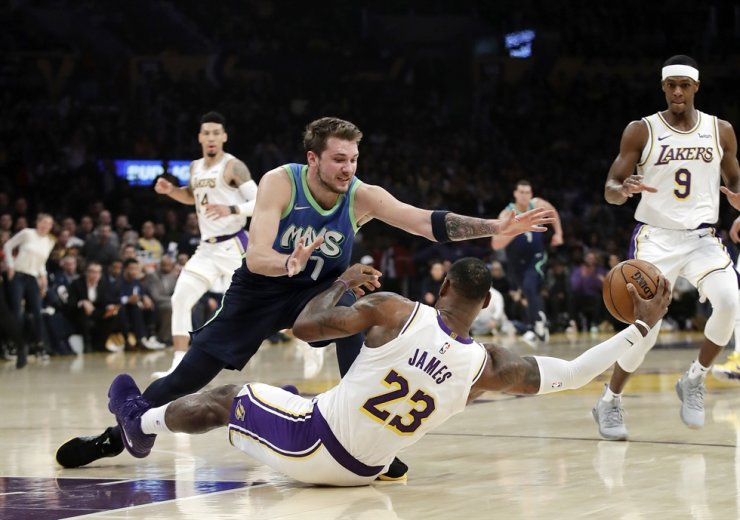 Los Angeles Lakers' LeBron James, right, recovers a loose ball under Dallas Mavericks' Luka Doncic during the first half of an NBA basketball game Sunday, in Los Angeles. /AP-Yonhap