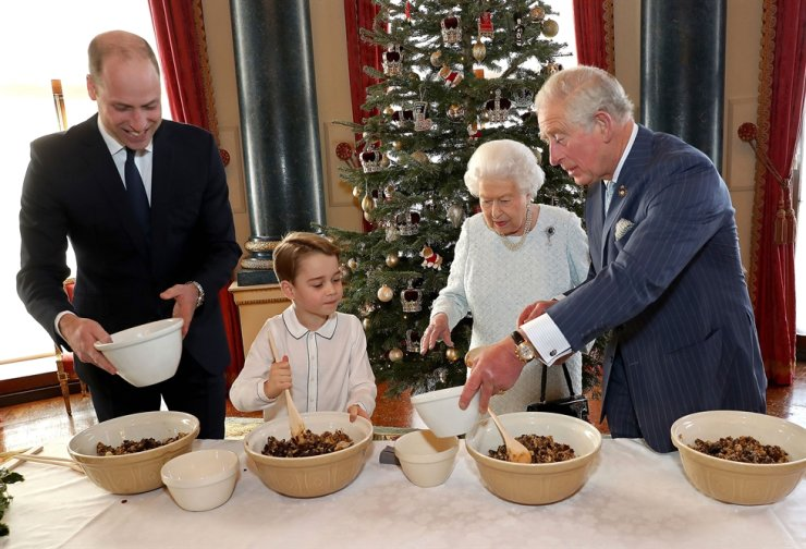 An undated handout photograph released by Buckingham Palace on December 21, 2019 shows (L-R) Britain's Prince William, Duke of Cambridge, Britain's Prince George of Cambridge, Britain's Queen Elizabeth II and Britain's Prince Charles, Prince of Wales preparing special Christmas puddings in the Music Room at Buckingham Palace in London, as part of the launch of The Royal British Legion's Together at Christmas initiative. AFP