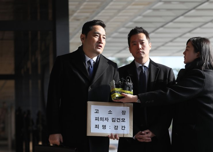 Lawyer Kang Yong-suk, left, holding a paper-wrapped criminal complaint against singer Kim Gun-mo, speaks to a reporter at Seoul Central District Prosecutors' Office on Monday. Yonhap