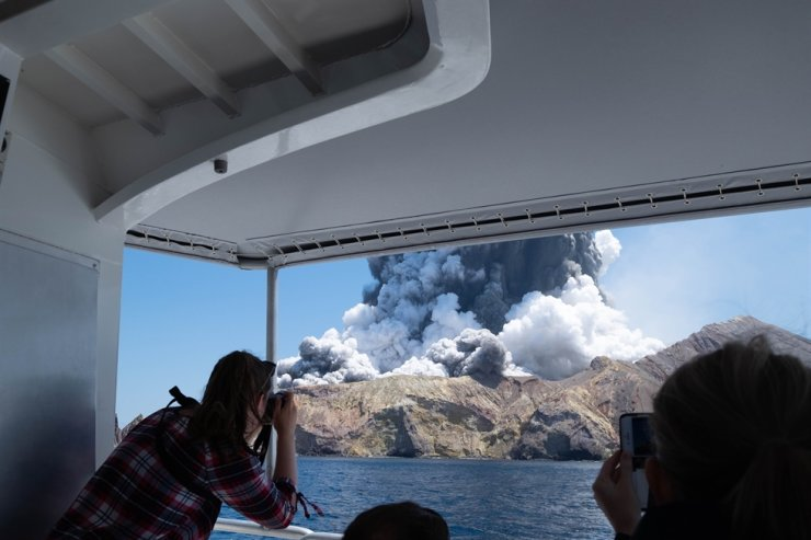 In this Dec. 9, 2019, file photo provided by Michael Schade, tourists on a boat look at the eruption of the volcano on White Island, New Zealand. The death toll from a volcanic eruption in New Zealand has risen to 19 after police said Monday that another person died at an Auckland hospital overnight. AP
