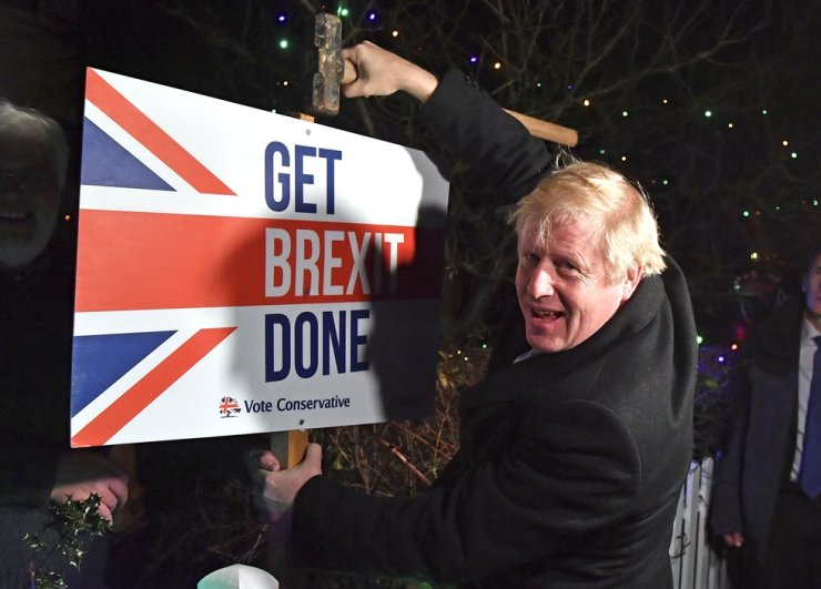 Britain's Prime Minister and Conservative party leader Boris Johnson poses as he hammers a 'Get Brexit Done' sign into the garden of a supporter, in Benfleet, east of London on Wednesday, Dec. 11, 2019, the final day of campaigning for the general election. AP