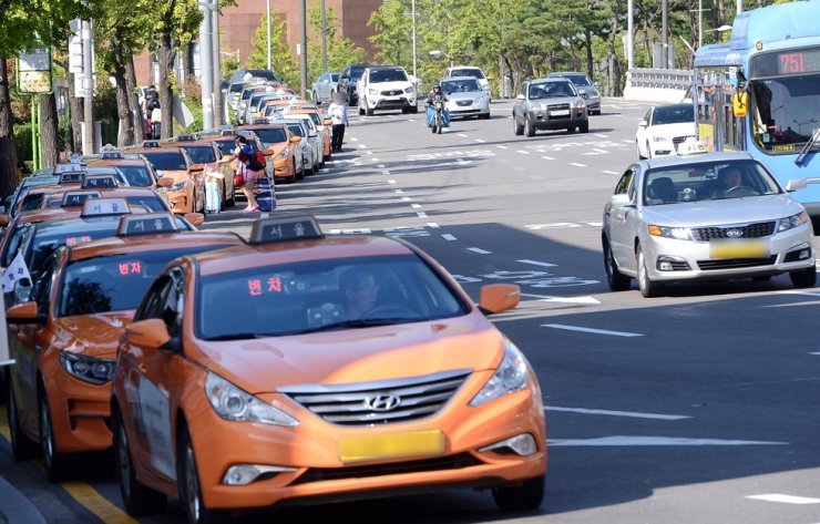 Taxis wait for passengers near Seoul Station in this file photo. A court recently ruled it was acceptable for a taxi company to automatically give a low rating on an elderly driver's health condition in a professional evaluation. Korea Times file