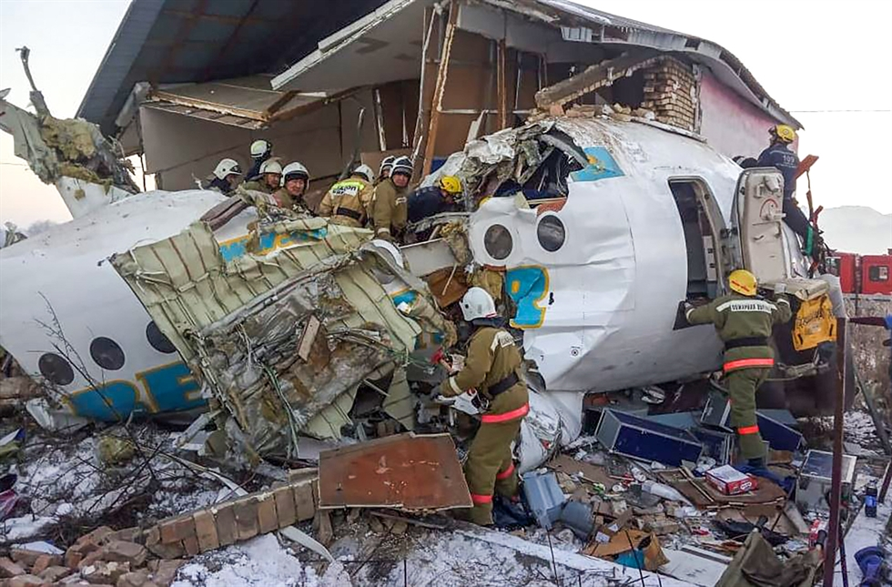 Police stand guard as rescuers assist on the site of a plane crashed near Almaty International Airport, outside Almaty, Kazakhstan, Friday, Dec. 27, 2019. The Kazakhstan plane with 98 people aboard crashed shortly after takeoff early Friday. AP