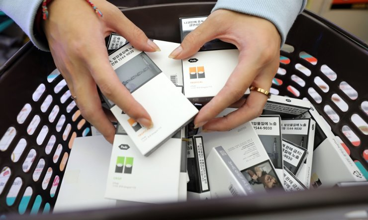 A clerk at a GS25 convenience store removes liquid e-cigarettes from shelves in this Oct. 24 file photo following the government's warning of possible health hazards. The Ministry of Food and Drug Safety announced Thursday that a substance causing serious lung injury has been found in e-liquid products sold here. / Yonhap