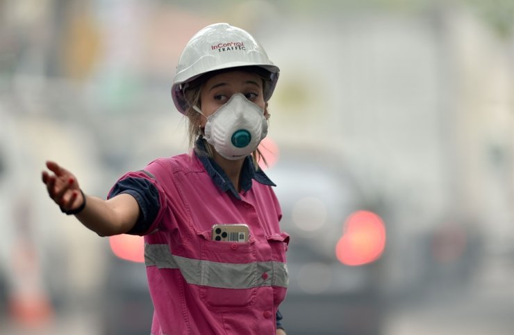 A traffic coordinator on a construction site wears a mask to protect against smoke pollution in Sydney on December 10, 2019. Toxic haze blanketed Sydney on December 10, triggering a chorus of smoke alarms to ring across the city, as Australians braced for 'severe' weather conditions expected to fuel deadly bush blazes. (Photo by PETER PARKS / AFP)