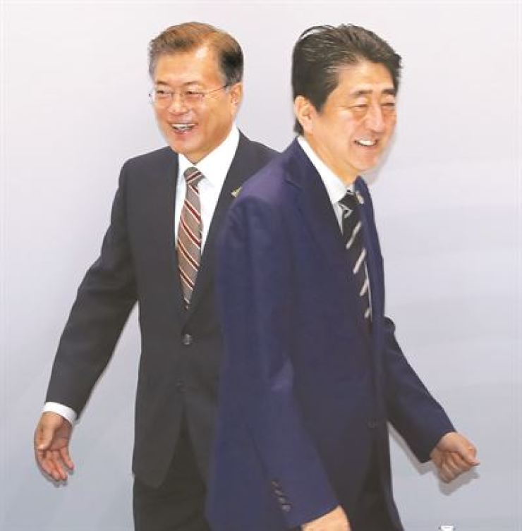 President Moon Jae-in, left, and Japanese Prime Minister Shinzo Abe walks past each other during a meeting in Hamburg, Germany in July 2017. / Yonhap