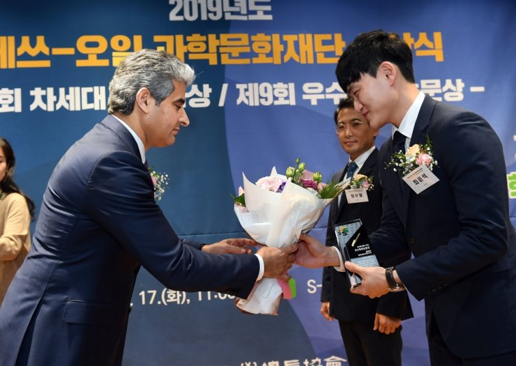 S-Oil CEO Hussain Al-Qahtani, left, presents flowers to an awardee during the refiner's awards ceremony for best theses and young scientists at its headquarters in Mapo-gu, Seoul, Tuesday. S-Oil awarded a total 115 million won to 10 researchers for their outstanding theses and presented a total 240 million won to six scientists in the fields of physics, chemistry, chemical engineering, energy and IT. Courtesy of S-Oil