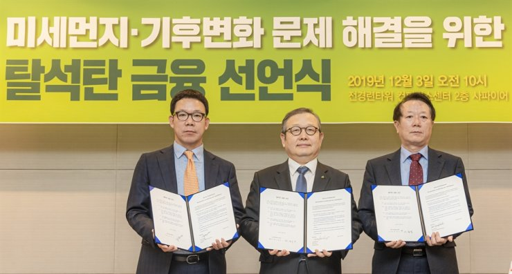 Korean Teachers' Credit Union's investment strategy department head Ga Seon-no, left, DB Insurance Vice President Chung Kyung-soo, center, and Public Official Benefit Association chief administrative officer Lee Chung-yeol hold a declaration on phasing out the financing of coal use at the FKI Tower in Seoul, Tuesday. The three joined other financial institutions that have declared they will not finance the construction of coal-fired power stations. / Courtesy of Korea Sustainability Investing Forum