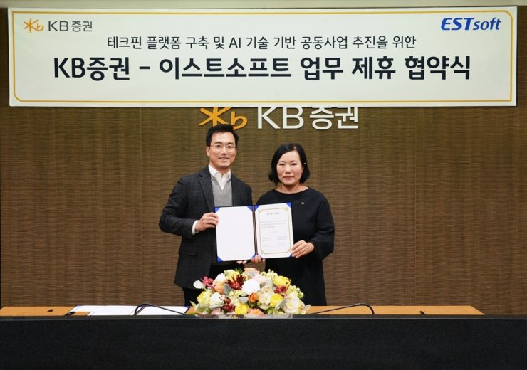 KB Securities CEO Park Jeong-rim, right, poses with ESTsoft CEO Chung Sang-won, after signing a partnership on financial technology at the former's headquarters on Yeouido in Seoul, Monday. Under the partnership, the software company will use its expertise in artificial intelligence to help the KB affiliate establish new financial platforms. Courtesy of KB Securities