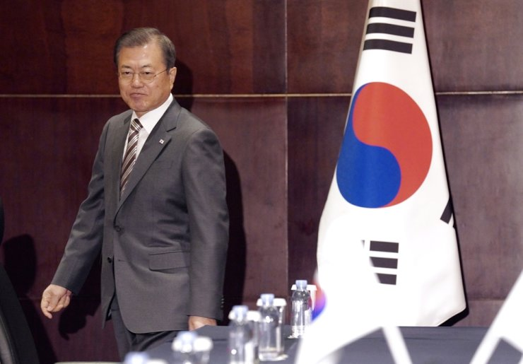 President Moon Jae-in goes to his seat after shaking hands with Japanese Prime Minister Shinzo Abe during a bilateral summit in Chengdu, China, Wednesday. Yonhap