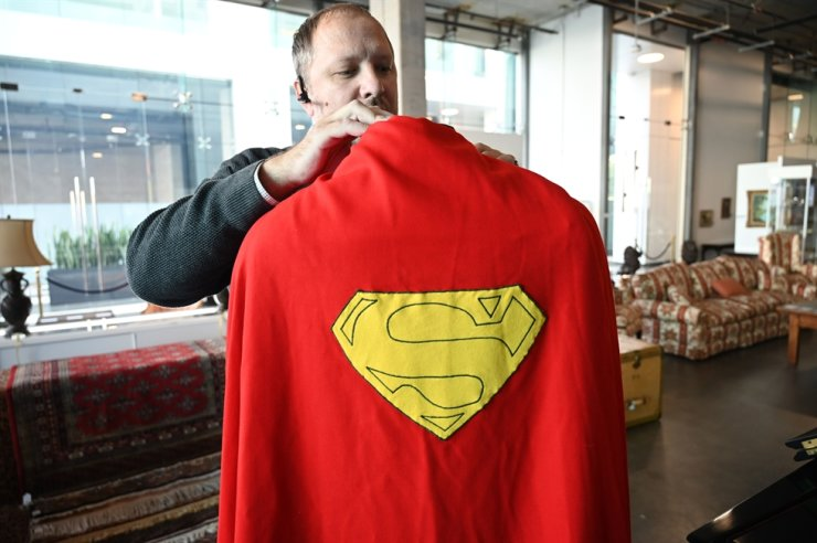 Julien's Auctions Jason DeBord adjust an original Superman cape worn by actor Christopher Reeve in the 1978 'Superman' film (estimate $100,000 -2000,000 $ USD) is displayed at Julien's Auctions house on Dec. 13, 2019, ahead of Julien's Icons & Idols: Hollywood Auction which takes place on Dec. 16, 2019. AFP