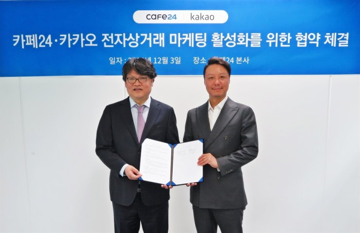 Cafe24 CEO Lee Jae-suk, left, and Kakao Vice President Shin Seok-chul pose for a photo after signing an MOU for vitalizing e-commerce marketing at Cafe24's headquarters in Seoul, Tuesday. / Courtesy of Cafe24