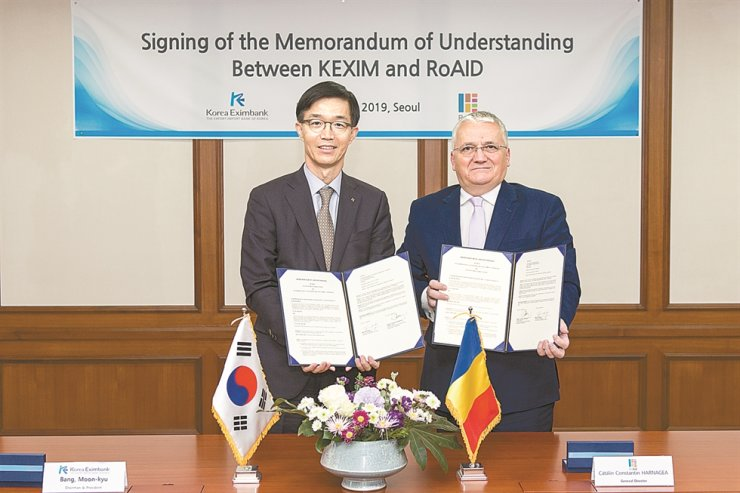 Export-Import Bank of Korea (Eximbank) CEO Bang Moon-kyu, left, poses with Romanian Agency for International Development General Director Catalin Harnagea, after signing an agreement for knowledge sharing on international development cooperation at Eximbank's headquarters on Yeouido in Seoul, Monday. / Courtesy of Eximbank
